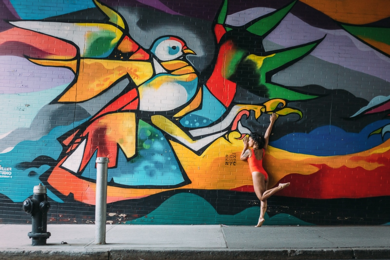 artist photography, dancer posing against a mural of colorful bird