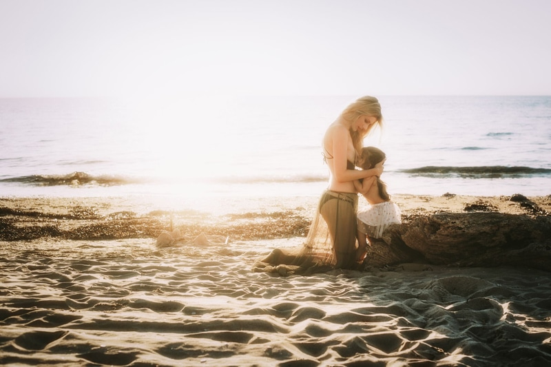 Motherhood and Maternity Photography, mother kneeling at beach to breastfeed daughter