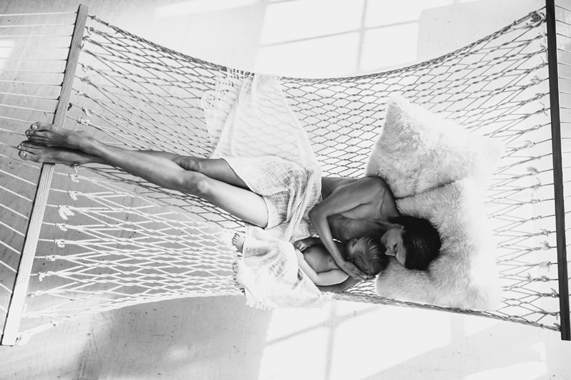 Motherhood and Maternity Photography, black and white of mother and child laying together in hammock, breastfeeding
