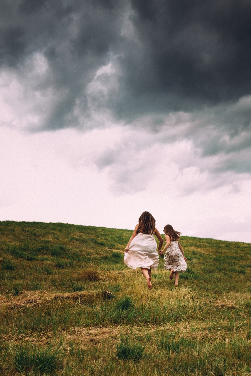 Children and Senior Photography, two girls running in a grass field away from the camera