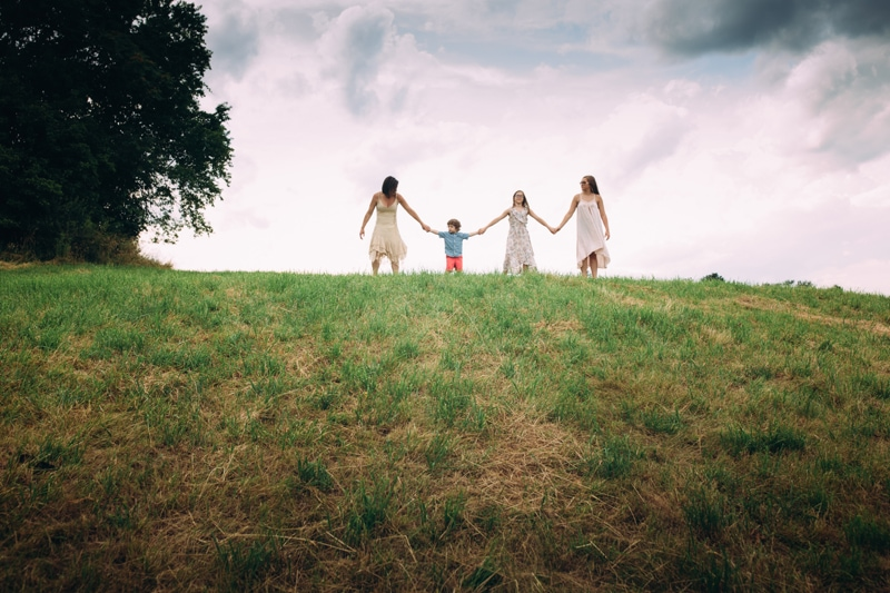 family photography, mother and children standing up on a hill