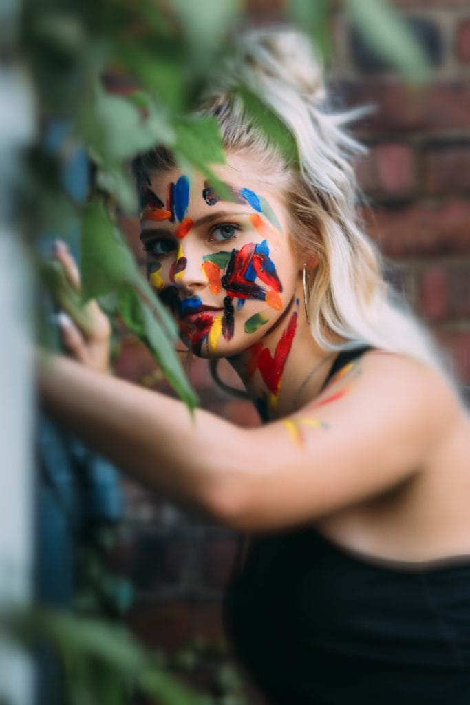 Senior Photography, Girl leaning against a wall with paint marks covering her face