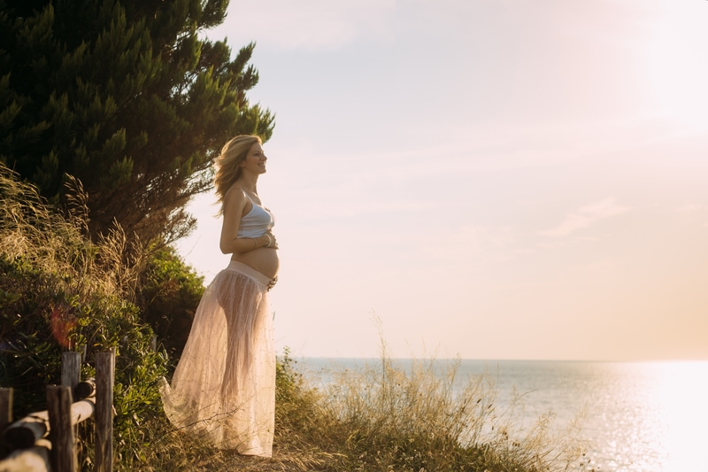 Motherhood and Maternity Photography, mother standing up on a hill next to the ocean
