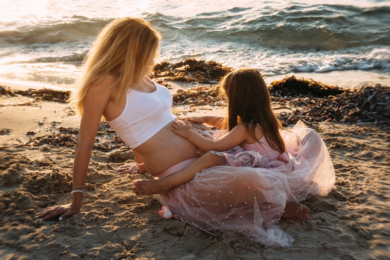 Motherhood and Maternity Photography, daughter playing with mother's belly