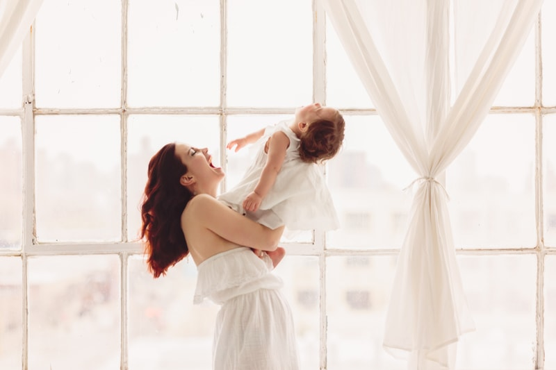 Motherhood and Maternity Photography, mother and child playing together in front of a window