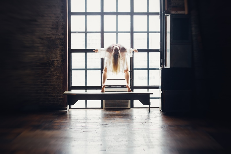 artist photography, dancer leaning backward next to window
