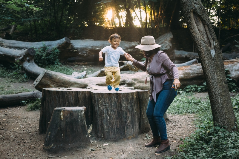 Motherhood and Maternity Photography, mother holding child's hand as he jumps from a stump