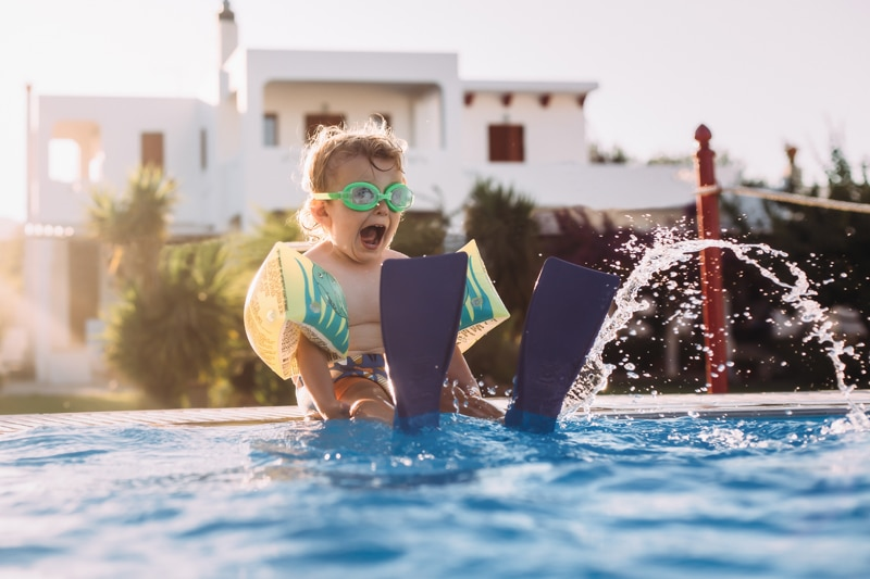 Children and Senior Photography, child with flippers playing at the edge of a pool