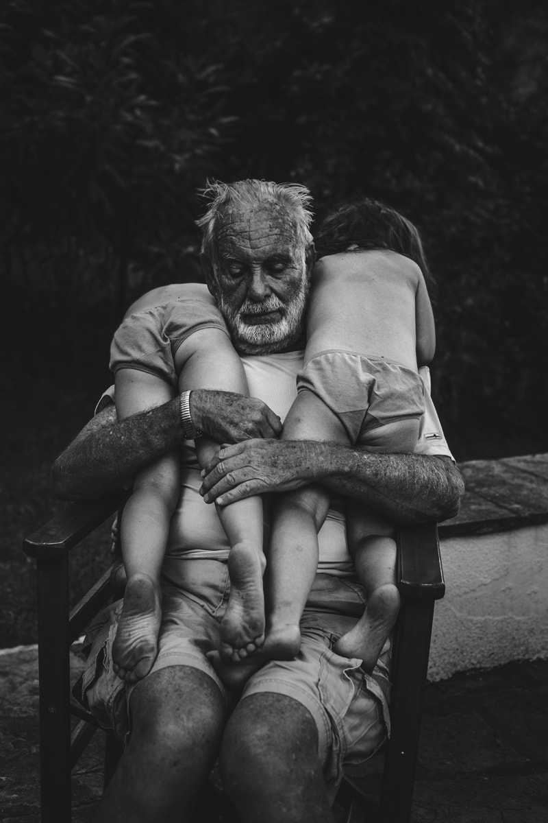 family photography, two children leaning over grandpa's shoulders