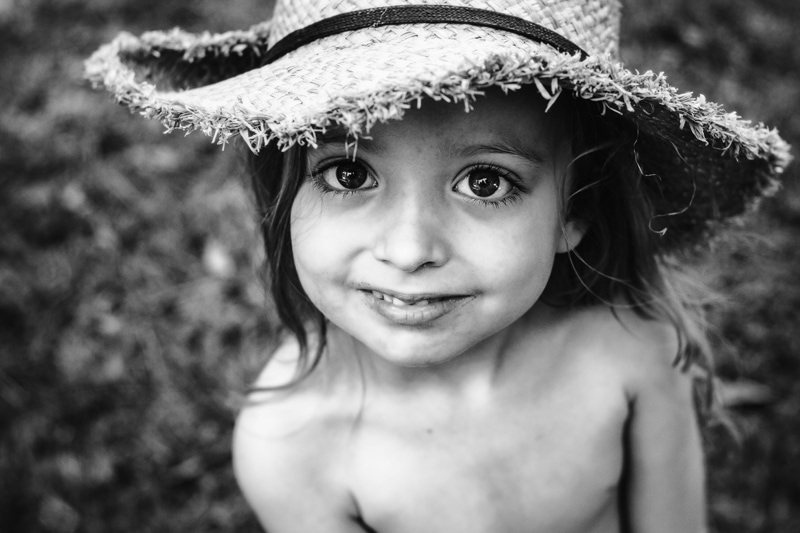 Children and Senior Photography, young child looking up at camera with a straw hat on