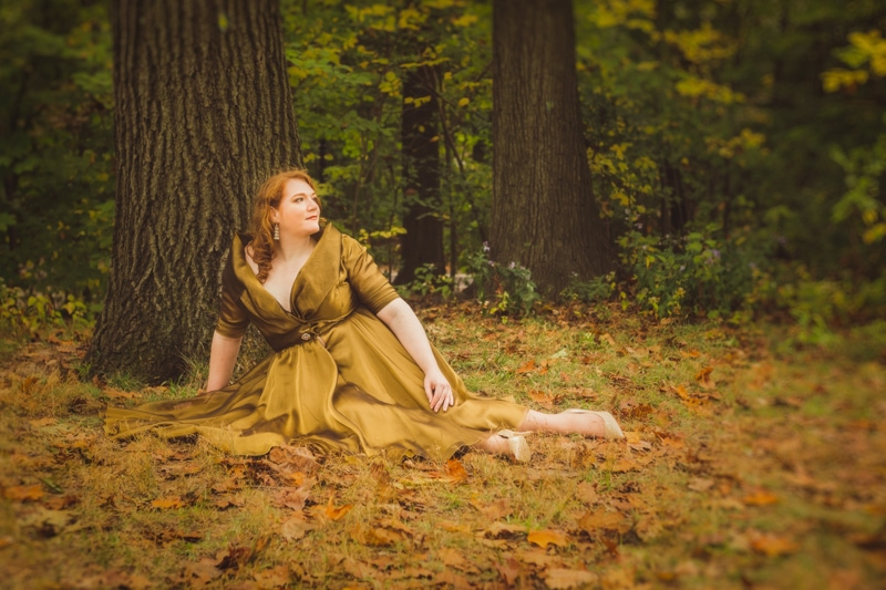 artist photography, woman sitting down in a bunch of leaves