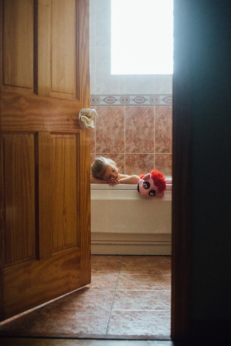 Children and Senior Photography, looking through a door at a child resting their head on the side of a bathtub