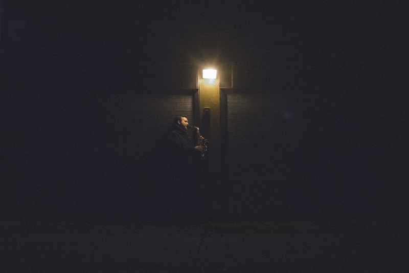 artist photography, man playing saxophone under a dim light