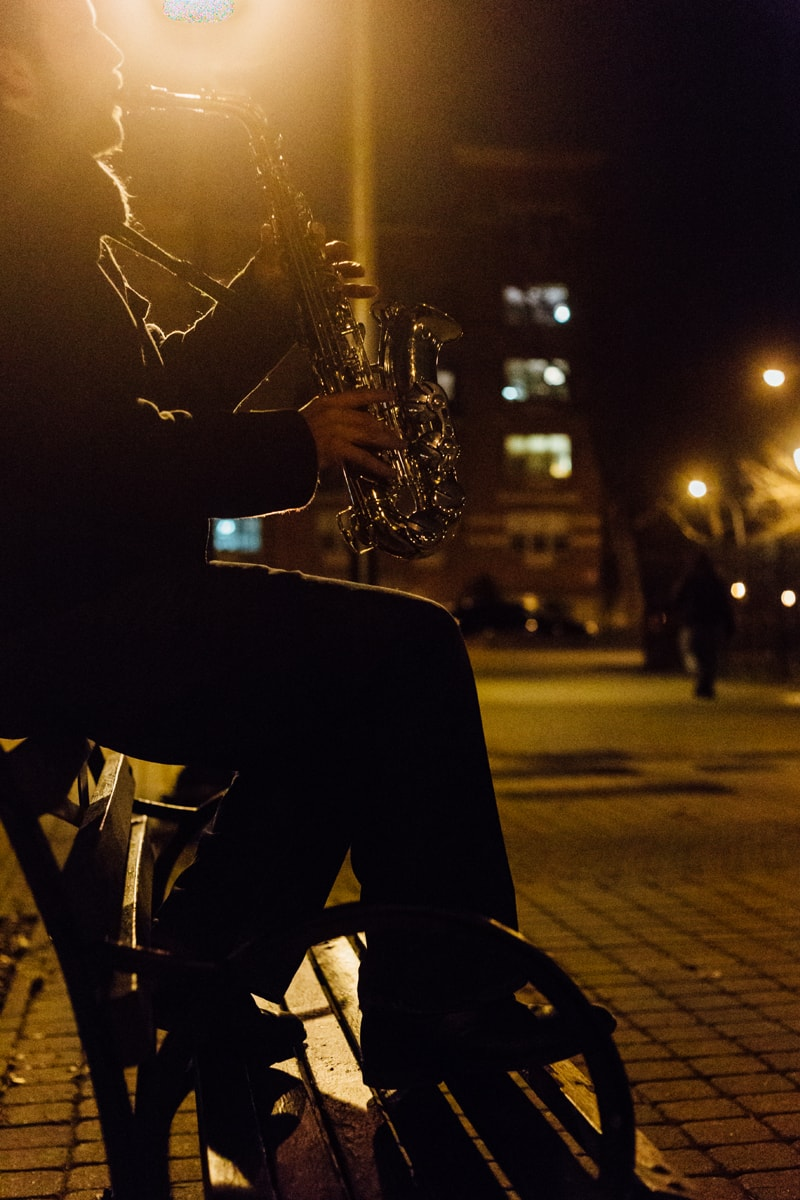 artist photography, man sitting on bench playing saxophone