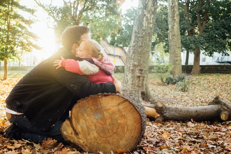 family photography, little girl hugging dad while sitting on a log