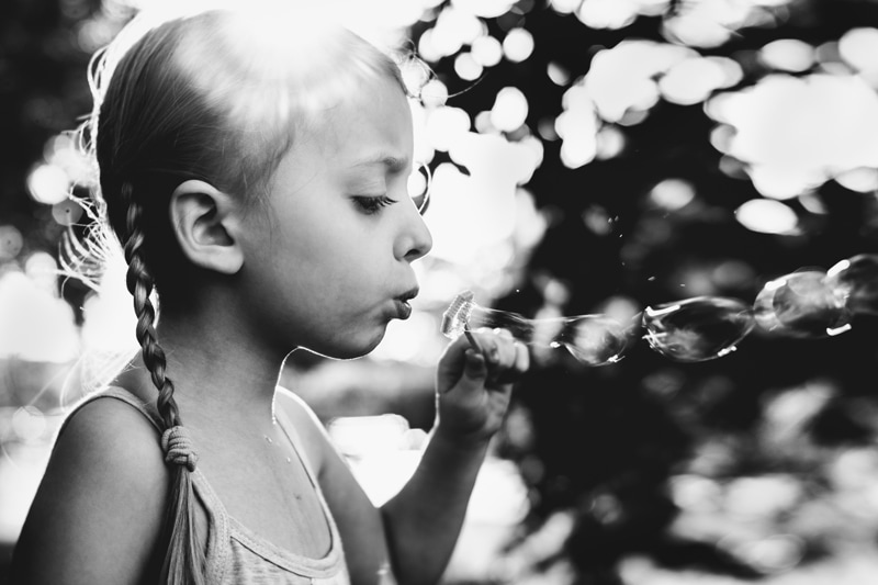 Children and Senior Photography, black and white of little girl blowing bubbles