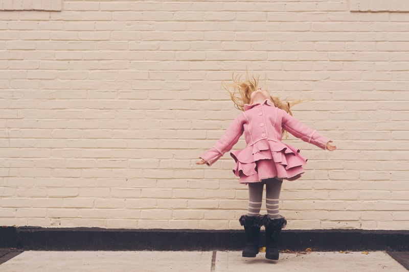Children and Senior Photography, little girl in pink coat jumping into the air