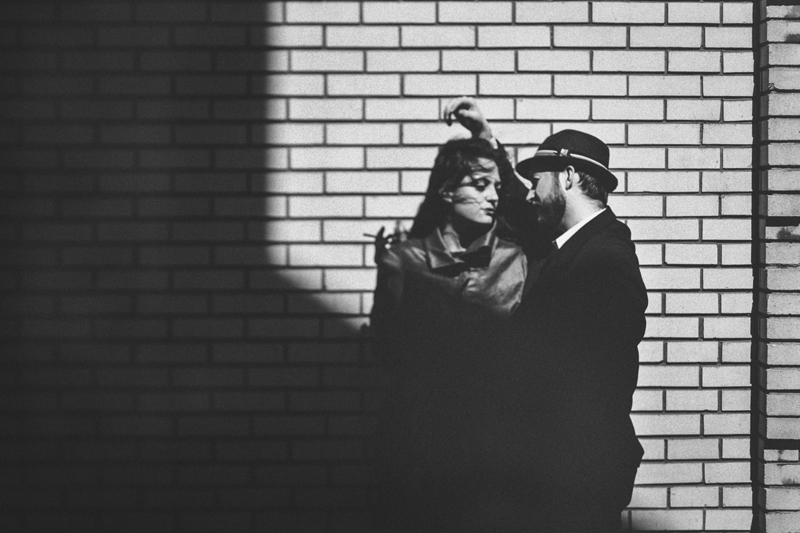 Couples Photography, couple leaning against a brick wall covered in shadows