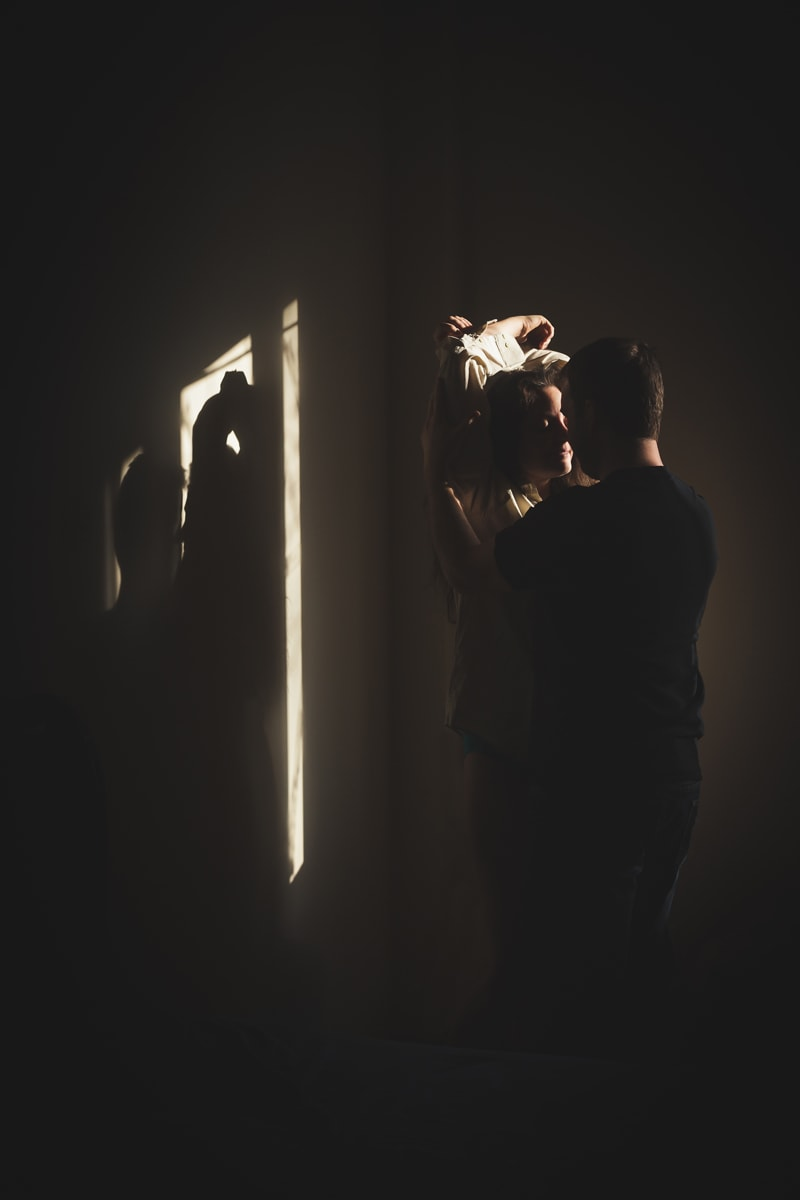 Sensual and Intimate Boudoir Photography, man rubbing his hands up a woman's arms in the shadowed corner of a room